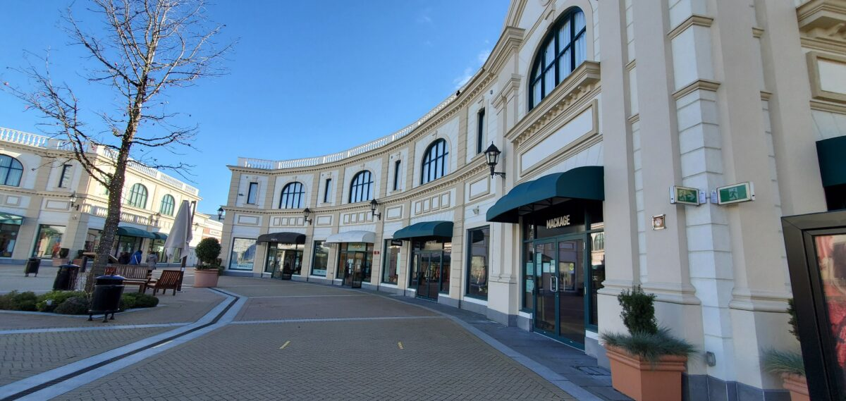 Row of Retailers circling the SEI statue at McArthur Glen Vancouver, including Ports, Maje and Mackage